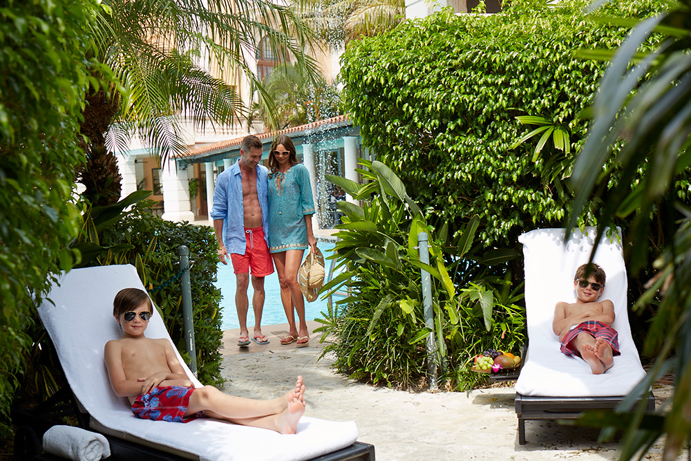 Family relaxing in cabana by the pool